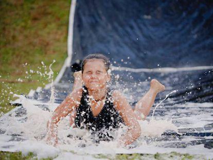 Una niña baja por un tobogán de agua.