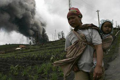 Una aldeana carga a su hijo mientras el volcán en erupción expulsa nubes de humo y cenizas.