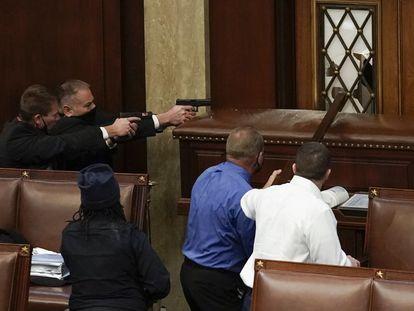 Unos policías apuntan con sus pistolas para proteger el acceso a la Cámara de Representantes estadounidenses de los asaltantes del Capitolio, este miércoles.
