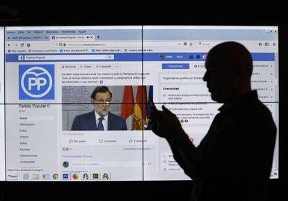 Un hombre frente a una pantalla con la página de Facebook del Partido Popular.