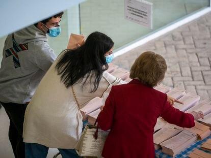 Varios votantes eligen las papeletas en un centro cultural en Mirasierra de Madrid.