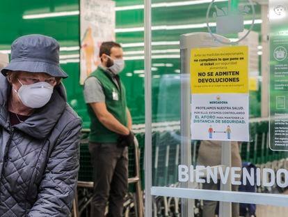 Una mujer con mascarilla a las puertas de un supermercado, a 16 de marzo de 2020.