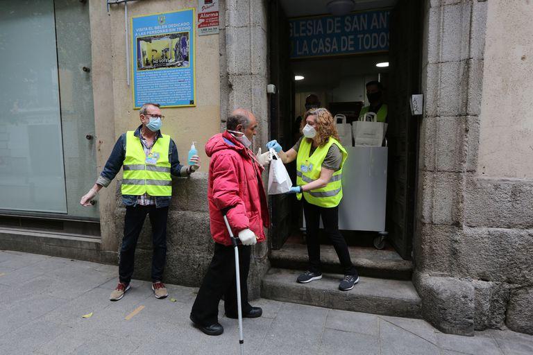 Una persona recoge una bolsa con alimentos en Madrid, el 13 de mayo, durante el confinamiento.